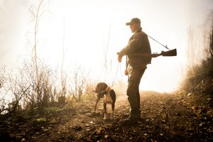 Hunter with rifle standing on gravel road and holding dog on a leash. Bright light is in the background.